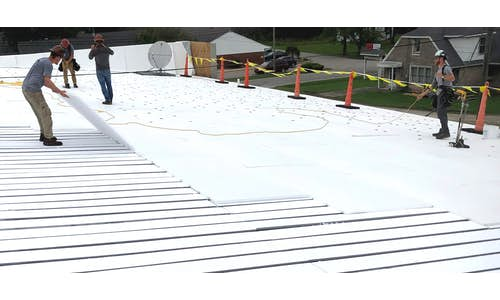 FR Composite Sheet being laid over Flute Fill in a metal re-roofing application