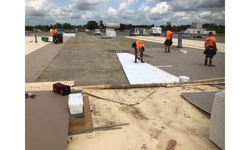 Pre-cut tapered cricket roofing insulation being installed